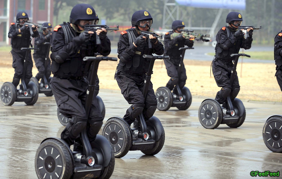 In this photo released by the official Xinhua news agency, members of China's armed police demonstrate a rapid deployment during an anti-terrorist drill held in Jinan, east China, on Wednesday July 2, 2008, roughly one month ahead of the Beijing Olympic Games. (AP Photo/Xinhua/Fan Changguo)