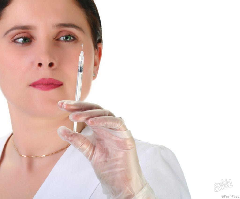 female nurse getting ready for injection, focus on  green eyes