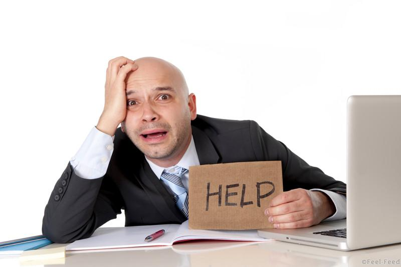 overworked unhappy bald business man in stress wearing suit holding help sign working on computer