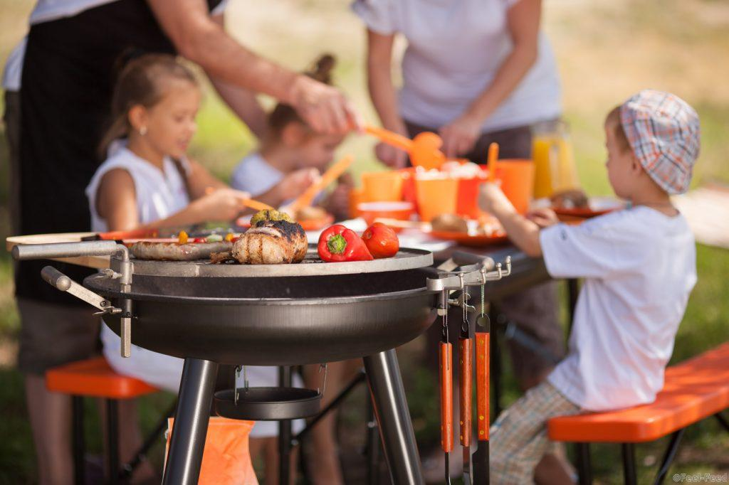 Family having a barbecue in the garden - focus on grilled food in the foreground