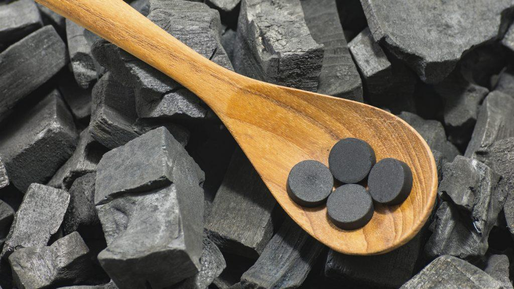 activated carbon pill in wood spoon on charcoal texture background