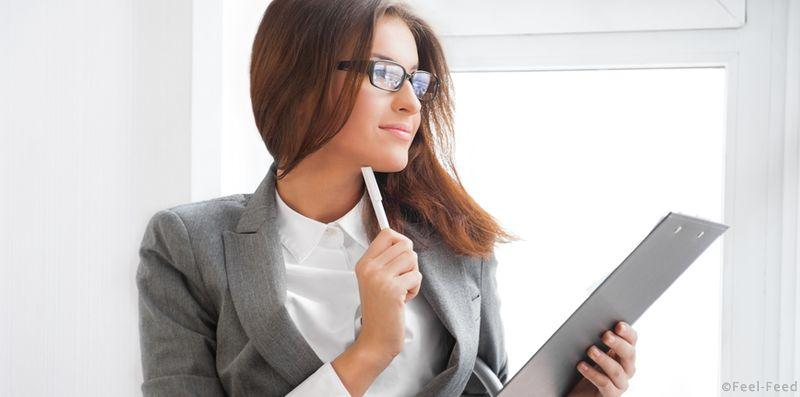 Beautiful business woman looking at papers she holding in her arms while working on computer at her office
