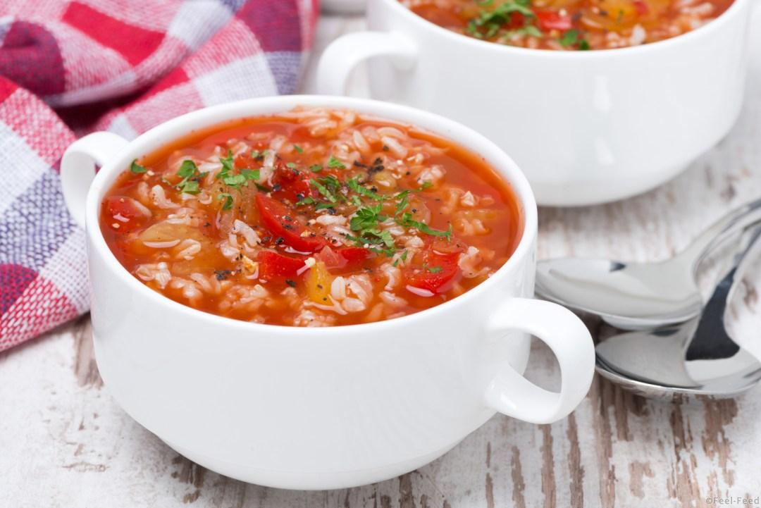tomato soup with rice and vegetables in a bowl, close-up