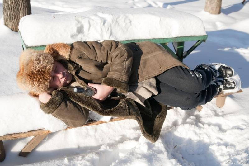 man in winter clothes slipping outdoor with alcohol bottle