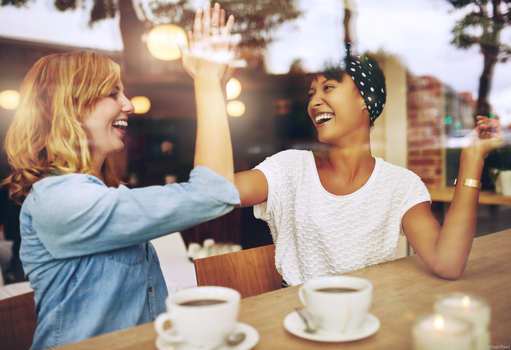 46416660 - happy exuberant young girl friends giving a high five slapping each others hand in congratulations as they sit together in a cafeteria enjoying a cup of hot coffee, multi ethnic viewed through glass